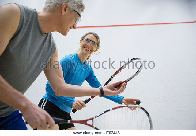 Couple in goggles playing squash - Stock Image
