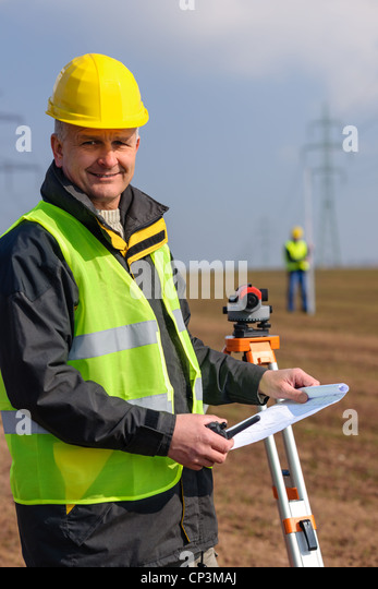 Land surveyors measuring with tacheometer hold construction plans on site - Stock Image