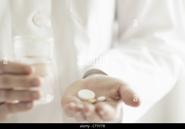 Doctor holding pills with glass of water - Stock Image