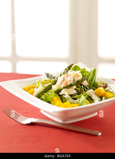 Asparagus crab mango salad near window - Stock Image