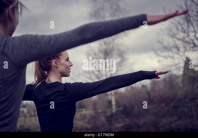 Cropped rear view of women arms open stretching, looking away - Stock Image
