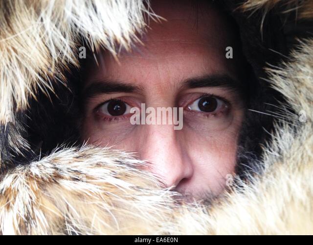 Portrait of man peering through fur lined hood - Stock Image