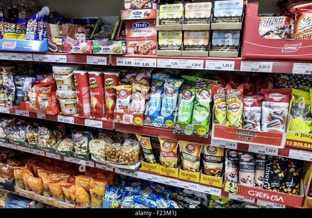 Madrid Spain Europe Spanish Salamanca snacks nuts chips Matutanos Pringles brand convenience store inside shelves - Stock Image
