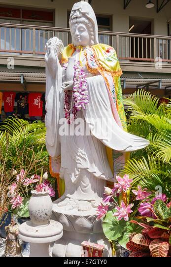 Honolulu Hawaii Hawaiian Oahu Chinatown shrine statue Buddha leis flowers - Stock Image