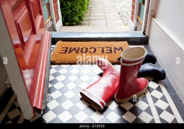 Welcome mat and wellington boots - Stock-Bilder