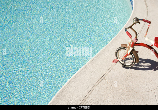 Child's tricycle at edge of swimming pool - Stock Image