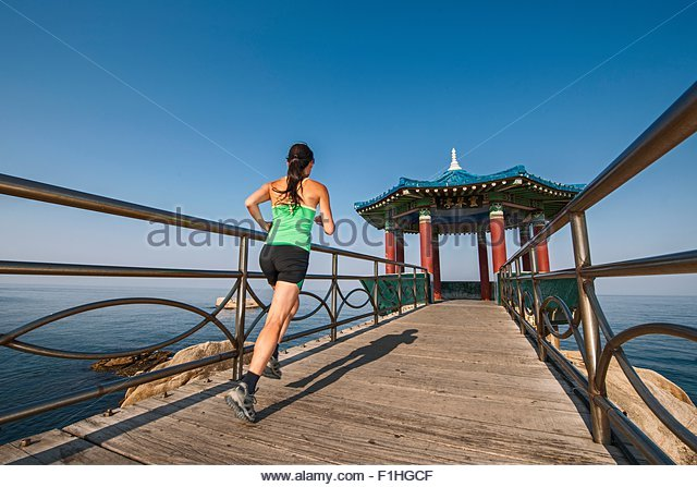 Mature woman running towards the sunrise pavilion, Sokcho, Gangwon, South Korea - Stock Image