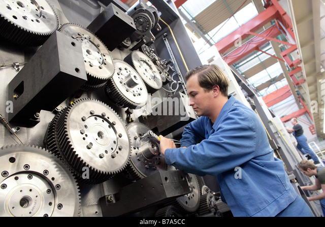 Laborer tightening the gears of an impression cylinder of a reel-fed offset printing machine, manufacture, Production - Stock Image