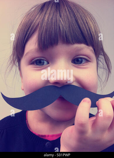 Child with paper mustaches - Stock Image