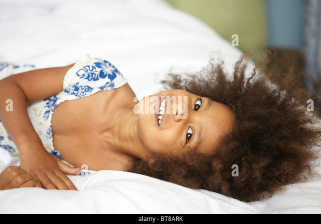 young mixed race girl, child laying on bed with white sheets in blue and white summer dress. - Stock Image