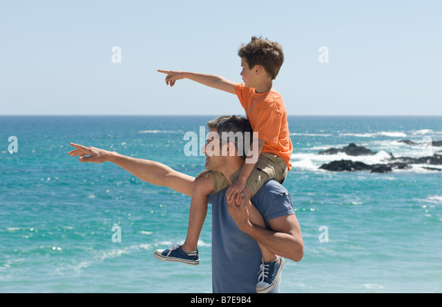 Father and son pointing at the sea - Stock Image