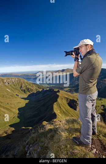 A hiker photographing the 'Val de Courre' in the Sancy Massif (Puy de Dôme France). Randonneur photographiant - Stock Image