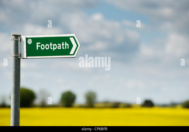 Footpath sign in front of a rape field in the English countryside - Stock Image