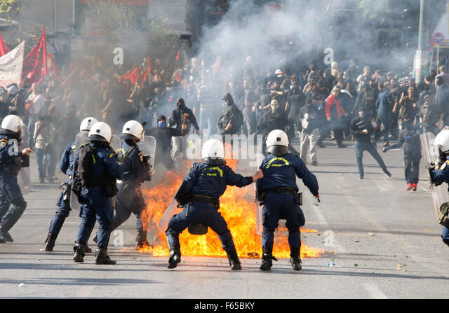Athens, Greece. 12th Nov, 2015. A riot policeman tries to avoid a petrol bomb thrown by protesters during a rally - Stock Image