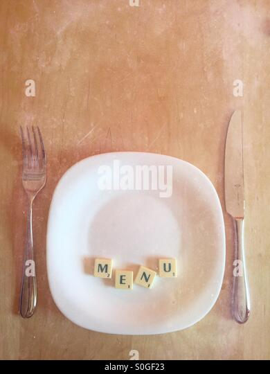 Plate with scrabble word MENU with chalkboard feel - Stock Image