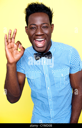 Joyful guy showing excellent gesture against yellow background - Stock Image