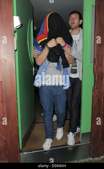 X Factor finalist Aiden Grimshaw chooses to hide under his jacket, as he leaves recording studio late night with - Stock Image