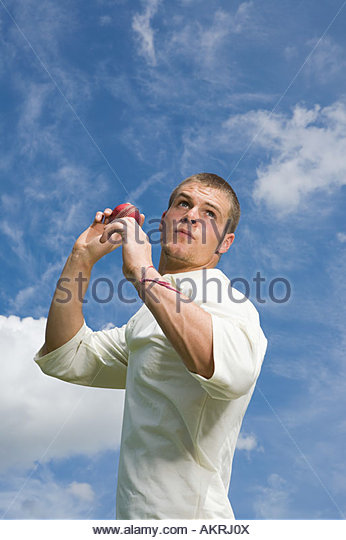 A cricket player throwing a cricket ball - Stock Image