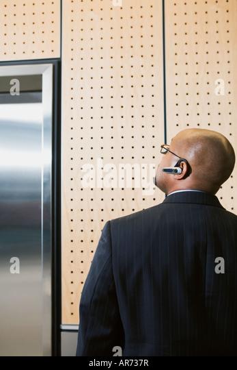 African businessman looking at elevator - Stock-Bilder
