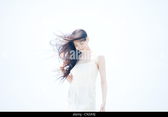 Young woman with long windswept black hair - Stock Image