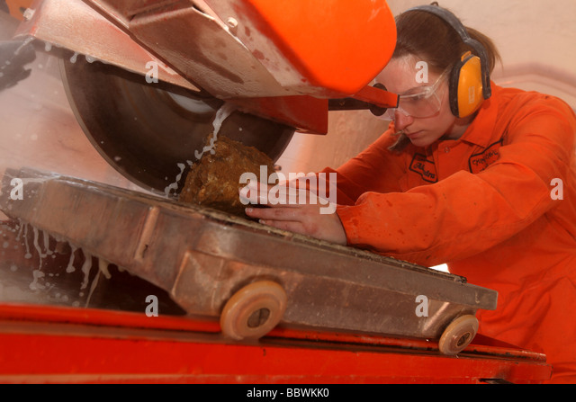 Scientist cutting up a Stalagmite sample on a circular bench saw in preparation for Climate Change Research. - Stock Image