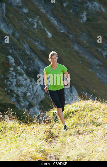Austria, Kleinwalsertal, Young woman running on mountain trail - Stock Image