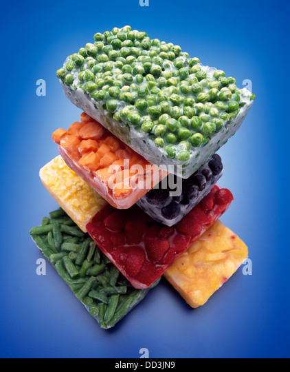 A large stack of frozen blocks of food; green peas, carrots, blackberries, corn, strawberries, peaches and green - Stock Image