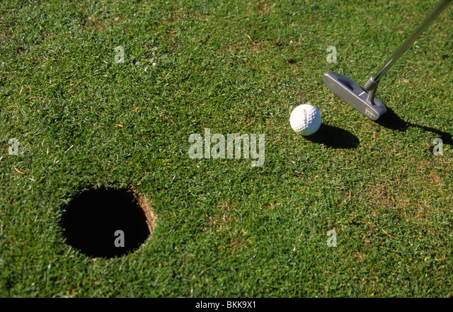 Person playing golf and putting a ball - Stock Image