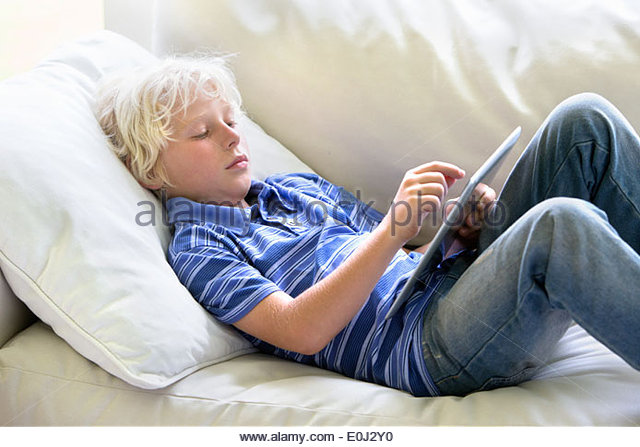 Boy using digital tablet on sofa - Stock-Bilder