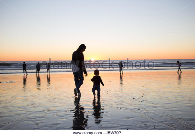 Silhouette of mother and baby boy on beach at sunset, Venice Beach, Los Angeles, California, USA - Stock-Bilder