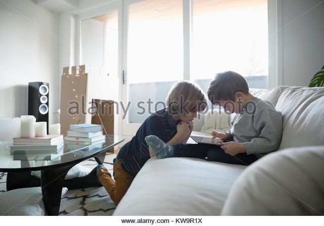Brothers using digital tablet on living room sofa - Stock Image