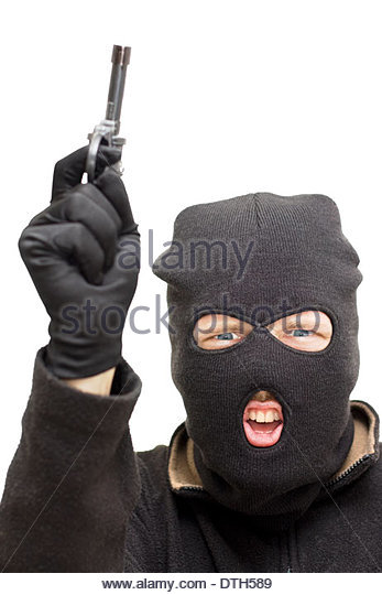 Studio Image Of A Balaclava Wearing Bandit Pointing His Gun Skywards During An Armed Holdup - Stock Image