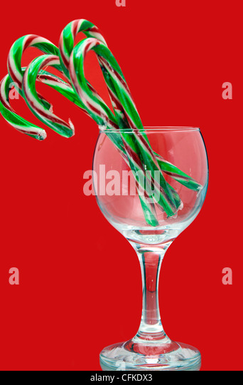 Festive still life of Christmas candy canes in a wine glass on a red background - Stock Image