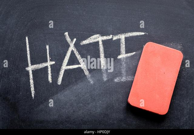 erasing hate, hand written word on blackboard being erased concept - Stock Image