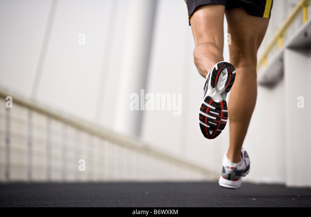 A man running across a bridge - Stock Image