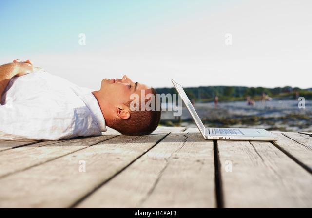 Man sleeping next to laptop on dock - Stock-Bilder