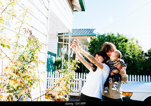 Woman taking family selfie at front of house - Stock-Bilder