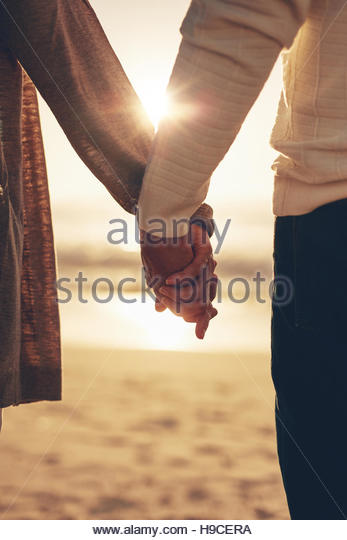 Close up rear view of a romantic senior couple holding hands against sea at sunset. - Stock Image