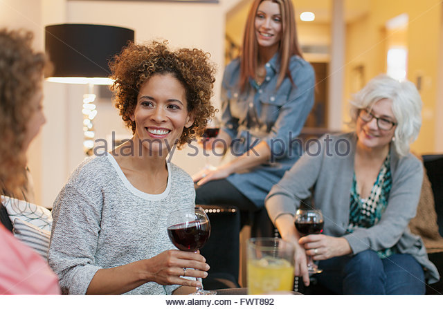 Friends enjoying some wine and conversation at home. - Stock Image