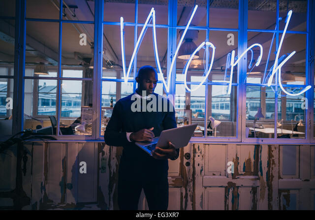 African young man standing in office using laptop computer. Business executive in office with big neon light work - Stock-Bilder