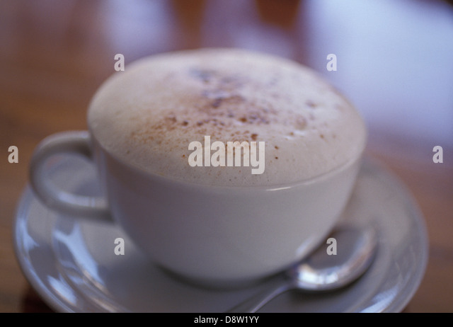Cappuccino (frothy coffee) in a white cup with saucer and teaspoon on brown table, with shallow depth of field - Stock Image