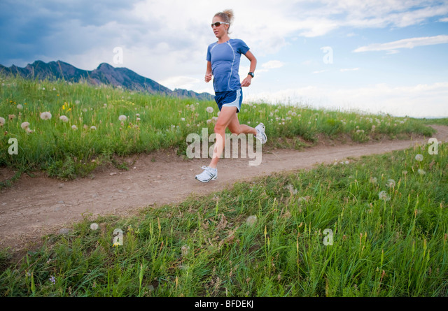 A female marathon runner trains on a trail in Boulder, Colorado. - Stock Image