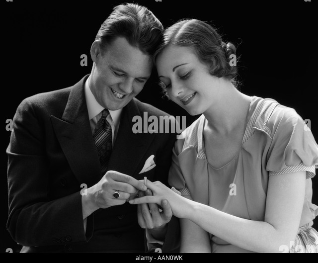1930s SMILING COUPLE SITTING HEADS PRESSED TOGETHER MAN PUTTING ENGAGEMENT RING ON WOMAN'S FINGER - Stock-Bilder