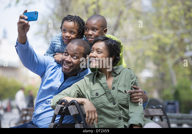 A family parents and two boys taking a photograph with a smart phone - Stock Image