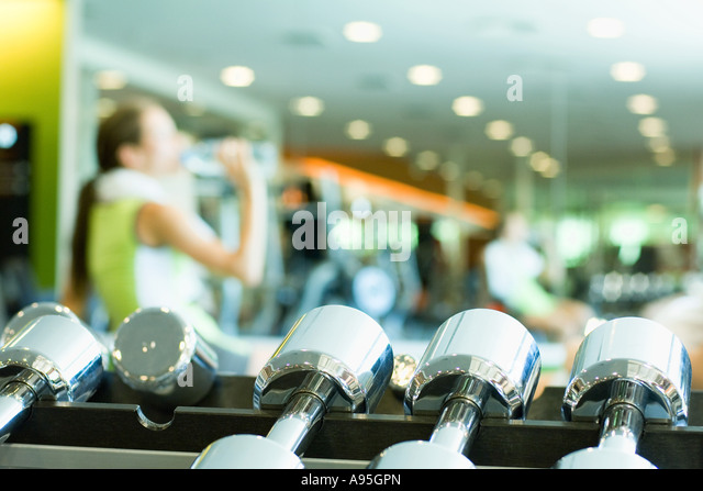 Woman drinking bottle of water, focus on rack of dumbbells in foreground - Stock Image