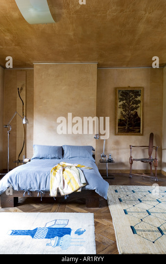 bedroom with stucco finish walls and Afghan carpet - Stock-Bilder