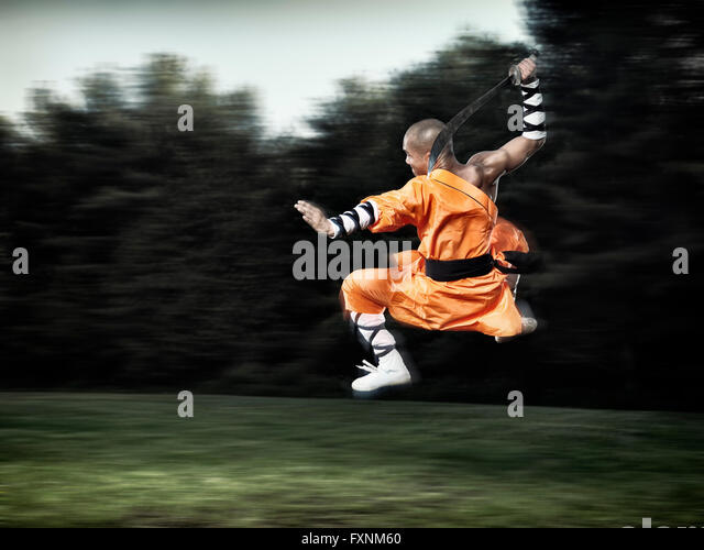Shaolin warrior monk in mid-air jump with a broad sword - Stock Image