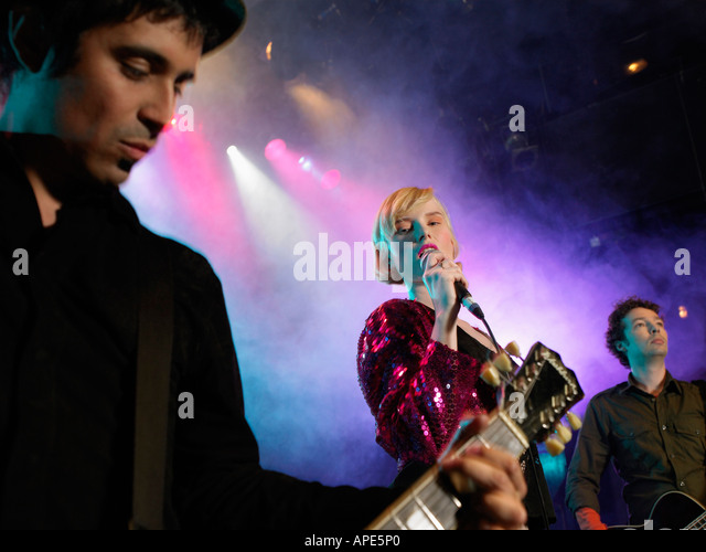 Rock band on stage in concert, low angle view - Stock Image