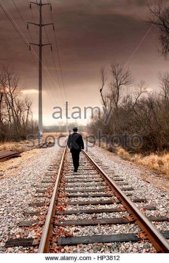 Well dressed young man walking away on tracks - Stock-Bilder