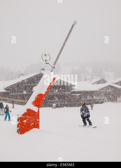 snow cannon beside a piste in heavy falling snow in the french alps with skiers and boarders behind - Stock Image